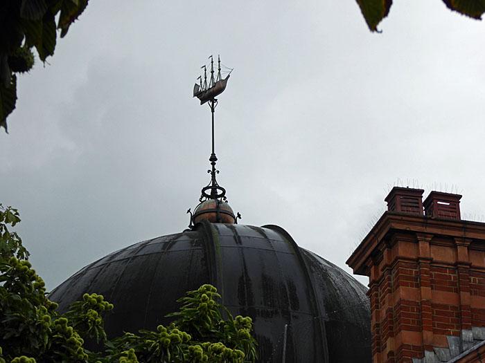 Foto van gebouw met koepel en windvaan