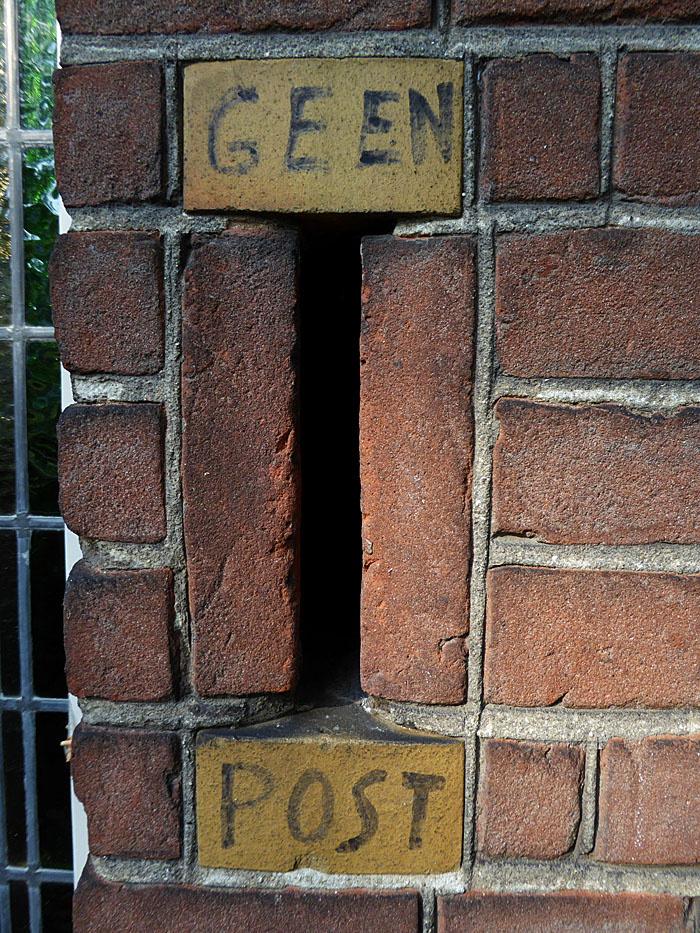 Foto van brievenbus in muur met tekst: Geen post