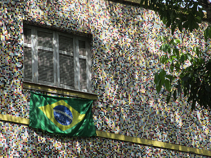 Foto van muur bedekt met mozaïek en raam met vlag
