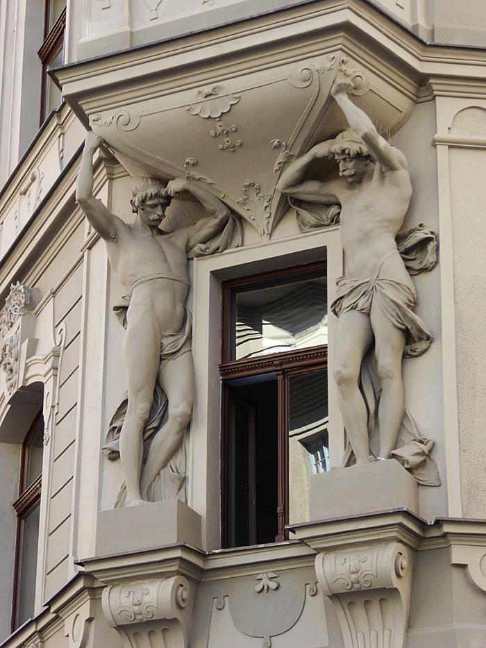 Foto van beelden van mannen, die balkon ondersteunen