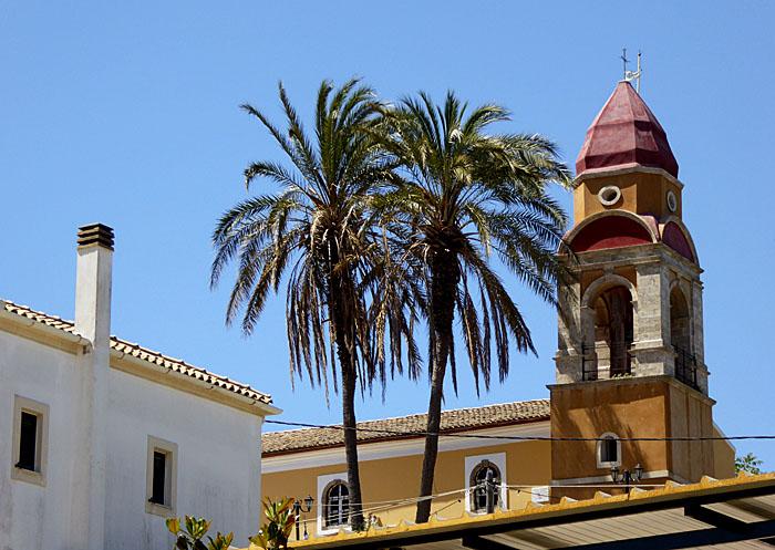 Foto van kerktoren en palmen